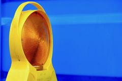 Yellow Road Construction Lantern Against Blue Container. Yellow road work lantern pictured in front of a blue container. Image taken in Munich. I like it because Stock Photography