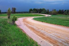 Yellow road on a green meadow. A yellow gravel dirt road winds on a green meadow before a summer thunderstorm with a blue sky Royalty Free Stock Photos