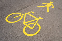 Yellow road marking indicating an bicycle path and pedestrian walkway Royalty Free Stock Photos