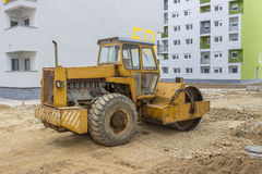 Yellow road roller in the new residential area Stock Images