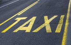 Yellow road sign on asphalt - taxi sign. Stock Photos