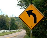 Yellow road sign indicating left turn. On country road royalty free stock images