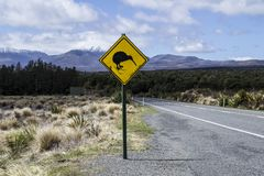 Yellow road sign with kiwi bird crossing by the road. Mountains in the background. Located in the Tongariro National Park, North. Island, New Zealand stock images