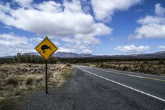 Yellow road sign with kiwi bird crossing by the road. Mountains in the background. Located in the Tongariro National Park, North. Island, New Zealand stock photo