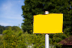 Yellow road sign pole and blue sky. With clouds on background with green trees Royalty Free Stock Photos