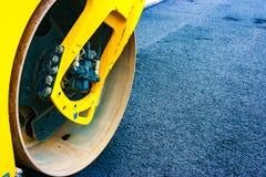 Yellow roadroller on newly laid asphalt. Detail of the front of a yellow roadroller on a newly laid asphalt stock photo