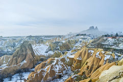 The yellow rocks of Pigeon Valley. The amazing landscape of the Pigeon Valley covered with snow and the misty Uchisar rock on the background, Cappadocia, Turkey Royalty Free Stock Image