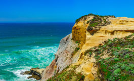 Yellow rocks and sand on portuguese coastline, vivid ocean water. Panoramic view Royalty Free Stock Photography
