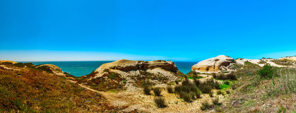 Yellow rocks and sand on portuguese coastline, vivid ocean water. Panoramic view Royalty Free Stock Image