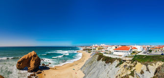 Yellow rocks and sand on portuguese coastline, vivid ocean water. Panoramic view Stock Image