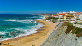 Yellow rocks and sand on portuguese coastline, vivid ocean water. Panoramic view Stock Photography