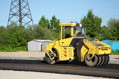 Yellow rolling machinery paving a road Royalty Free Stock Photos