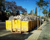 Yellow rolloff container is filled by debris Royalty Free Stock Photos