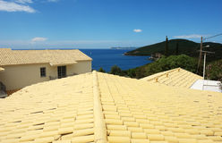 Yellow roofs and blue sea in Greece. Royalty Free Stock Images