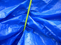 Yellow rope on blue tarpaulin. Yellow rope tieing up a blue tarpaulin makes a complex and interesting pattern Stock Photo