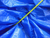 Yellow rope on blue tarpaulin. Yellow rope tieing up a blue tarpaulin makes a complex and interesting pattern Stock Photography