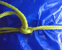 Yellow rope on blue tarpaulin. Yellow rope tieing up a blue tarpaulin makes a complex and interesting pattern Stock Images