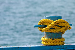 Yellow Rope on Bollard. Heavy yellow rope tied to a blue bollard with water as background Stock Photos