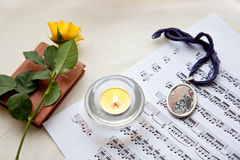 Yellow rose. Beautiful yellow rose on a book with notes and burning candle Stock Photos