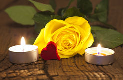 Yellow rose and candles. One yellow rose blossom and two tea lights with a red wooden heart on wooden board Royalty Free Stock Image
