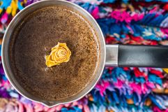 Yellow rose in coffee on colorful background royalty free stock image