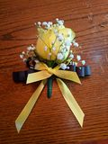 Yellow corsage on wood. Yellow rose corsage with baby& x27;s breath and yellow and black ribbons on a wood surface stock image