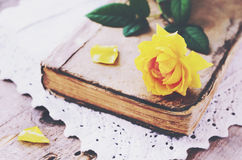 Yellow rose laying upon vintage book on lace doily Royalty Free Stock Photos