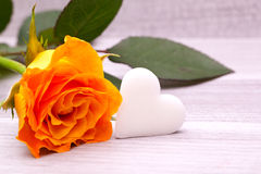 Yellow rose with white sugar heart decoration Stock Photo