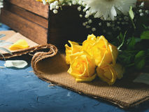 Yellow roses on blue and burlap. Bunch of yellow roses on blue textured background. Floral still life Stock Photography