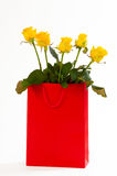 Yellow roses bouquet in a red paper bag, isolated on white background Royalty Free Stock Image