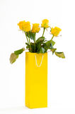 Yellow roses bouquet in a yellow paper bag, isolated on white background. Royalty Free Stock Image