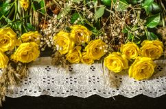 Yellow roses with dry branches and white embroidered edging lay on the black plywood Royalty Free Stock Photography