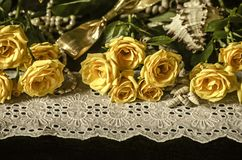 Yellow roses,dry branches of white gypsophila,reeds on white lace border with beads pearls on black background. Sprigs with yellow roses, dry branches of white stock photos