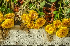 Yellow roses,dry branches and white lace border,covered with amber beads on a black background. Sprigs with yellow roses,dry branches of white gypsophila and royalty free stock photos