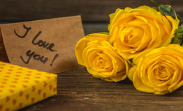 Yellow roses, gift box and card with text I love you Stock Photo