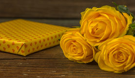 Yellow roses and gift box  on a old wooden table.  Royalty Free Stock Photo