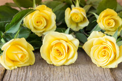 Yellow roses lying on wooden background Stock Image