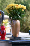 Yellow roses in vase. On grave in cemetery Stock Photos