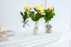 Yellow roses in white jug on white table against neutral background royalty free stock photos