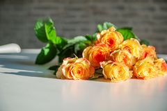 Yellow roses on a white wooden table. Holidays and celebration concept royalty free stock image