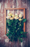 Yellow roses and a wooden frame Stock Photos