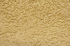Yellow rough plaster on wall Stock Photos