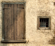 Yellow rough wall and windows. Small window and big closed window with brown shutters. Rough, yellow or beige wall of an old house in a small Italian town or Stock Photos
