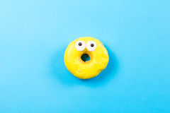 Yellow round donut with eyes on blue background. Flat lay, top view. Royalty Free Stock Photo