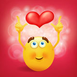Yellow round smiley face with pink heart Royalty Free Stock Image