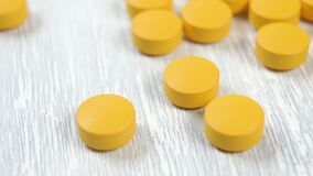 Yellow round vitamin tablets glide and appear slowly on a wooden light table.