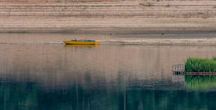 Yellow row boat with blue oars. Next to a sandbar in a river with a grassy island in the right foreground Royalty Free Stock Images