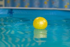 Yellow rubber ball floats in the children`s pool. For background royalty free stock photo