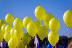The yellow rubber balloons filled with gas against the blue sky. Royalty Free Stock Images