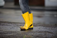 Yellow rubber boots in a dirty puddle Royalty Free Stock Photos